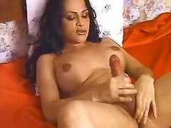 Attractive shemale masturbates solo on red bedsheet