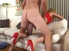 Guy hard fucks young curly shemale in red on sofa